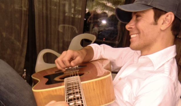 Photo of Christopher Spiewak playing the guitar and smiling in Boulder Colorado.